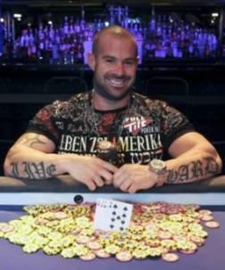 Un tatuatissimo Erik Cajelais mostra felice il braccialetto appena vinto
